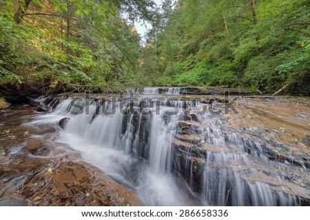 Tiered Cascading Waterfall Over Wide Ledge at Sweet Creek Falls Trail Complex in Mapleton Oregon - stock photo