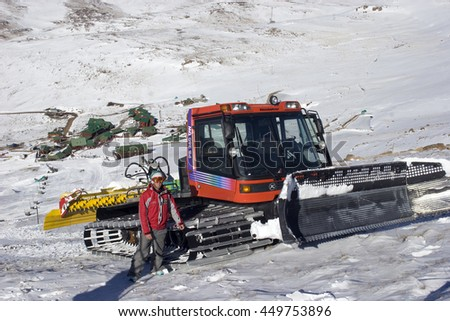 TIFFINDELL, SOUTH AFRICA - 07 JULY: A man stands next to his slope groomer at the top of the slope at Tiffendell, South Africa's only ski resort. Tiffendell is situated in the Drakensberg Mountains. - stock photo