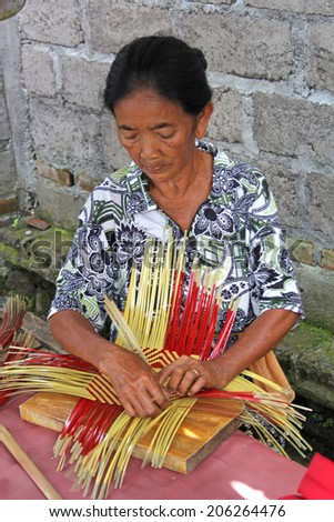 TIGA WASA, INDONESIA-APRIL 16, 2014:  A Balinese woman demonstrates the making of a traditional basket made from bamboo and with the local colors of the village on April 16, 2014. - stock photo