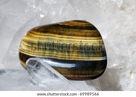 Tiger eye gem energized on druze of quartz crystals. This gem is used as a jewel stone and also in alternative medicine and esoterics (connected with 3rd chakra). - stock photo