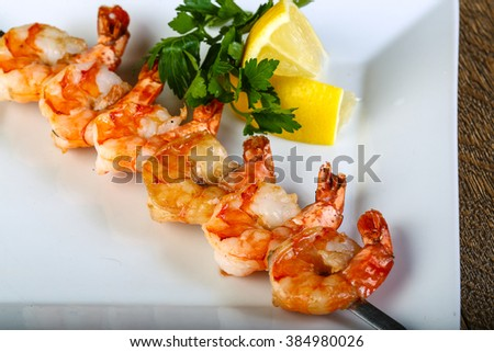 Tiger prawn skewer served sliced lemon and parsley