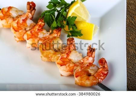Tiger prawn skewer served sliced lemon and parsley - stock photo