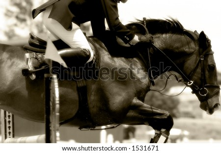 Tight close-up image of horse & rider clearing a jump in an equestrian showjumping event #2 (soft focus, sepia tone). - stock photo