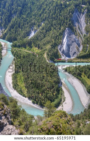 tight river bend filled with light blue water of Rhine Canyon in Switzerland seen from Flims and train Glacier Express coming out of a tunnel - stock photo