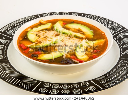 Tight shot of bowl of tortilla soup in white bowl on graphic black and white charger plate.  Ancient Aztec Geometric Pattern on plate. - stock photo
