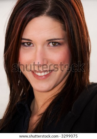 tightly cropped headshot of beautiful young brunette (red highlights) woman smiling at camera. white background.  black polo shirt. plane of sharp focus is the eyes