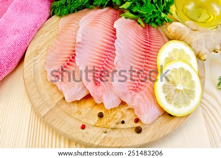 Tilapia fillets, dill, parsley, lemon, ginger, cloth, vegetable oil on a wooden boards background - stock photo