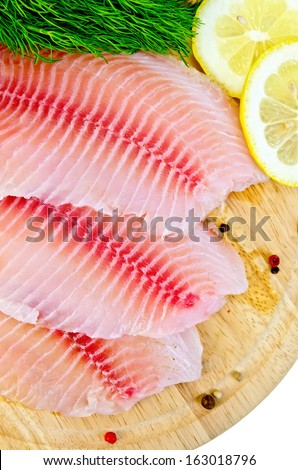 Tilapia fillets with dill, lemon and pepper on a wooden board isolated on white background - stock photo