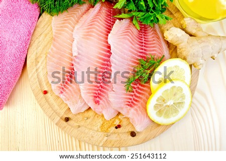 Tilapia fillets with dill, lemon, ginger, cloth, vegetable oil on a wooden boards background - stock photo