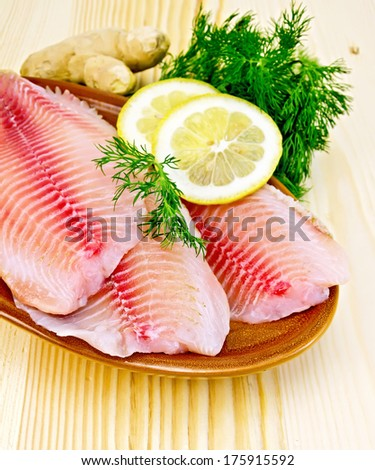 Tilapia fillets with lemon and dill in pottery, ginger root on the background of wooden boards - stock photo