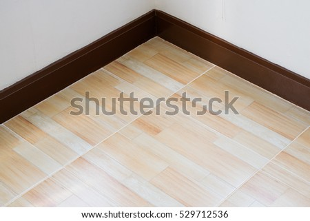 Tile floor in corner with brown tone pattern, white wall, interior empty room