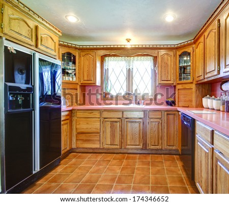 Tile floor kitchen room with black refrigerator, decorated wood cabinets
