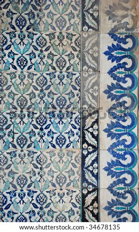 tiled and bordered grunge ceramic wall of a mosque - stock photo