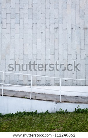 Tiled wall with a blank gray bricks  and stairs