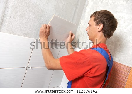 tiler installing wall tile at home repair renovation work - stock photo