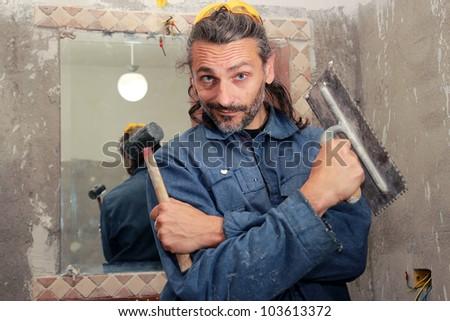 Tiler poses in a bathroom installing ceramic tiles - stock photo