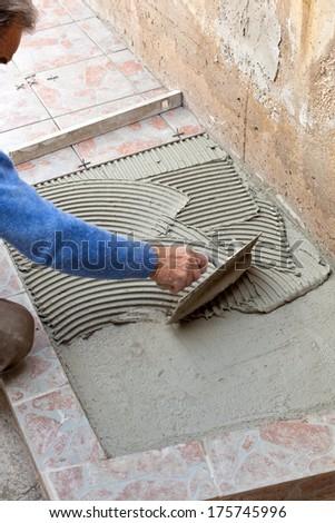 Tiler to work with tile flooring for garden - stock photo