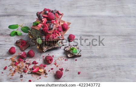 Tiles of a broken exquisite hand-made chocolate with dried and fresh berries, nuts hazelnuts, grated chocolate, peel, mint, clean empty place for text, for the recipes - stock photo