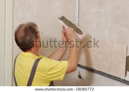 tiling - man installs ceramic tile - stock photo