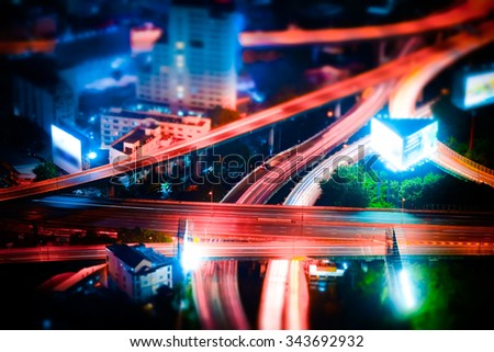 Tilt shift blur effect. Abstract cityscape background. Futuristic night aerial view of highway interchange with moving cars. Bangkok, Thailand - stock photo