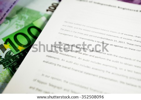 Tilt-shift effect on audit report detail next to european currency - stock photo