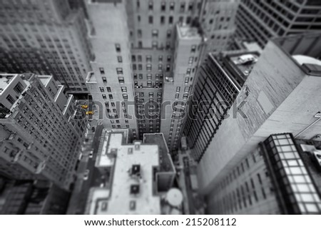 Tilt-shift looking down at yellow cabs in the streets of New York, USA, as small colorful dots in black and white composition of tall skycrapers with limited depth of field leading to miniature look - stock photo