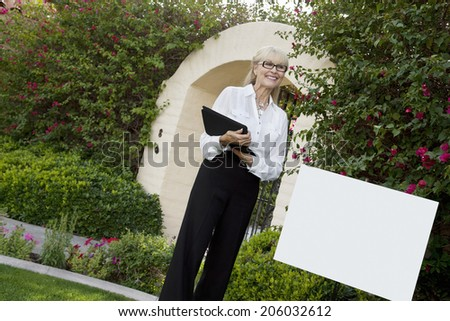 Tilt shot of cheerful senior agent standing by sign board with clipboard - stock photo