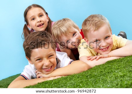 Tilt up of happy children having rest lying on the grass and looking at camera - stock photo