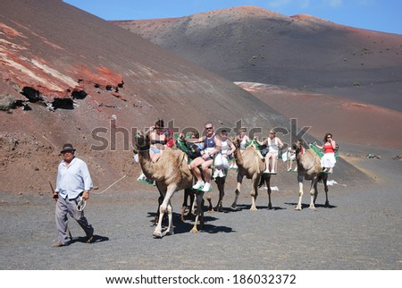 TIMANFAYA, LANZAROTE - 29 OCTOBER: Tourists riding camels in Timanfaya National Park in Lanzarote on October 29, 2009 - stock photo