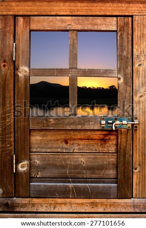 Timber door with window to sunset and river - stock photo