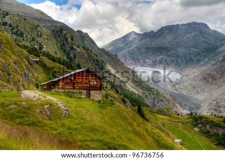 timber hut in front of Aletsch glacier valley - stock photo