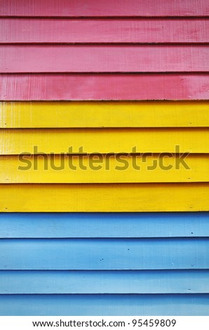 Timber plank wall painted with red, yellow and blue color paint. - stock photo
