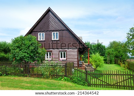 Timbered countryside house with a green backyard - stock photo