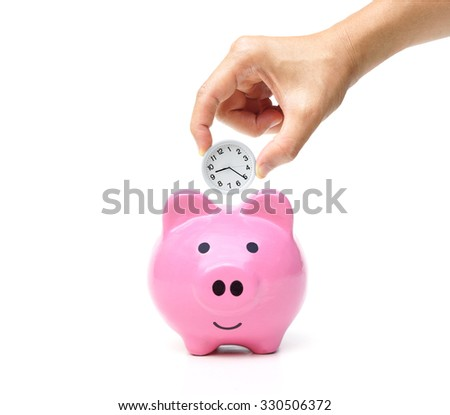 Time and money - hand putting a clock into a pink piggy bank                                           - stock photo