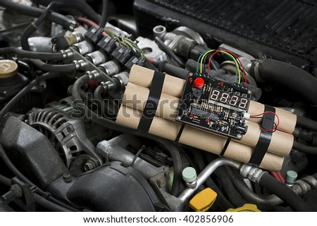 Time bomb explosive with digital countdown timer deployed on a car engine.        - stock photo