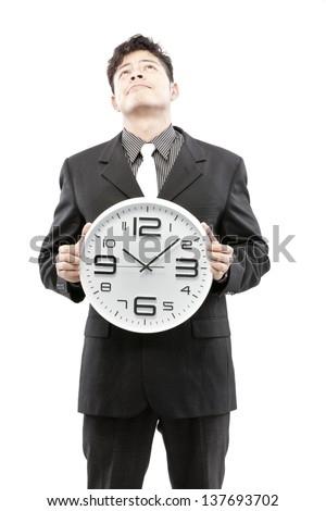 Time concept,Businessman holding big clock and give the expression on his face - stock photo