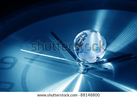 Time concept. Closeup of glass globe lying on blue metal clock face - stock photo