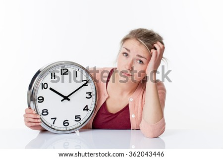 time concept - confused beautiful young blond woman displaying a clock disappointed and annoyed by schedule, white background