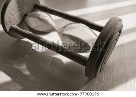 time concept with hourglass lying toned in warm black and white - stock photo