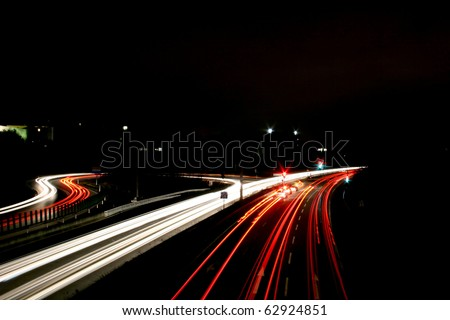 Time exposure photo with a street at night and automobile headlights of a multiple lane city street and a traffic light, seen at the Autobahn near Auestadion in Kassel, Germany - stock photo