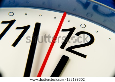 Time - Extreme closeup clock hands about to hit midnight or noon - stock photo