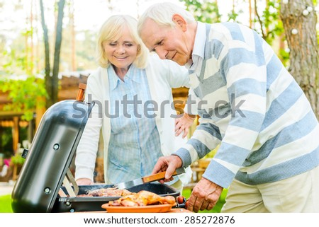 Time for barbeque. Happy senior couple barbecuing meat on the grill while standing at the back yard of their house - stock photo