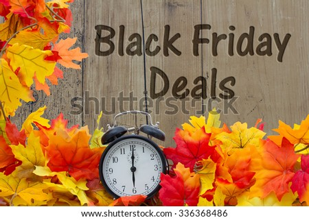 Time for Black Friday Shopping Deals, Autumn Leaves and Alarm Clock with grunge wood with text Black Friday Deals - stock photo