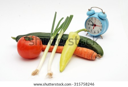 Time for diet. blue alarm clock and fresh food