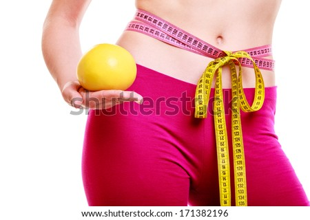 Time for diet slimming. Fit fitness woman measure tape around her waist fruit in hand, weight loss concept. Isolated on a white background. - stock photo