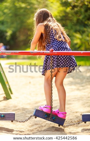 Time for fun. Summer holidays concept. Little funny girl having fun on playground. Child using kids equipment. Enjoyable playful kid outdoors.  - stock photo