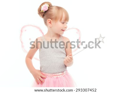 Time for magic. Nice little girl wearing fairy costume and holding wand while keeping her glance down