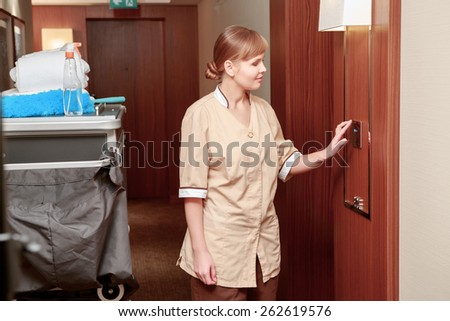 Time for room service. Smiling hotel maid in beige uniform checks climate indicators in the hall of the hotel standing just by the maid trolley  - stock photo
