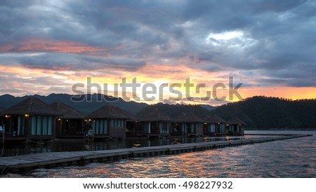 time for sunset at wooden housing raft in dam on water with cloudy sky