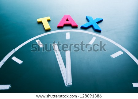Time for tax concept, color word and clock on blackboard - stock photo